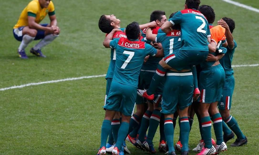 O atacante Hulk, autor do único gol brasileiro, já nos acréscimos, observa a comemoração dos jogadores do México no fim da partida Foto: Paul Hanna / AP