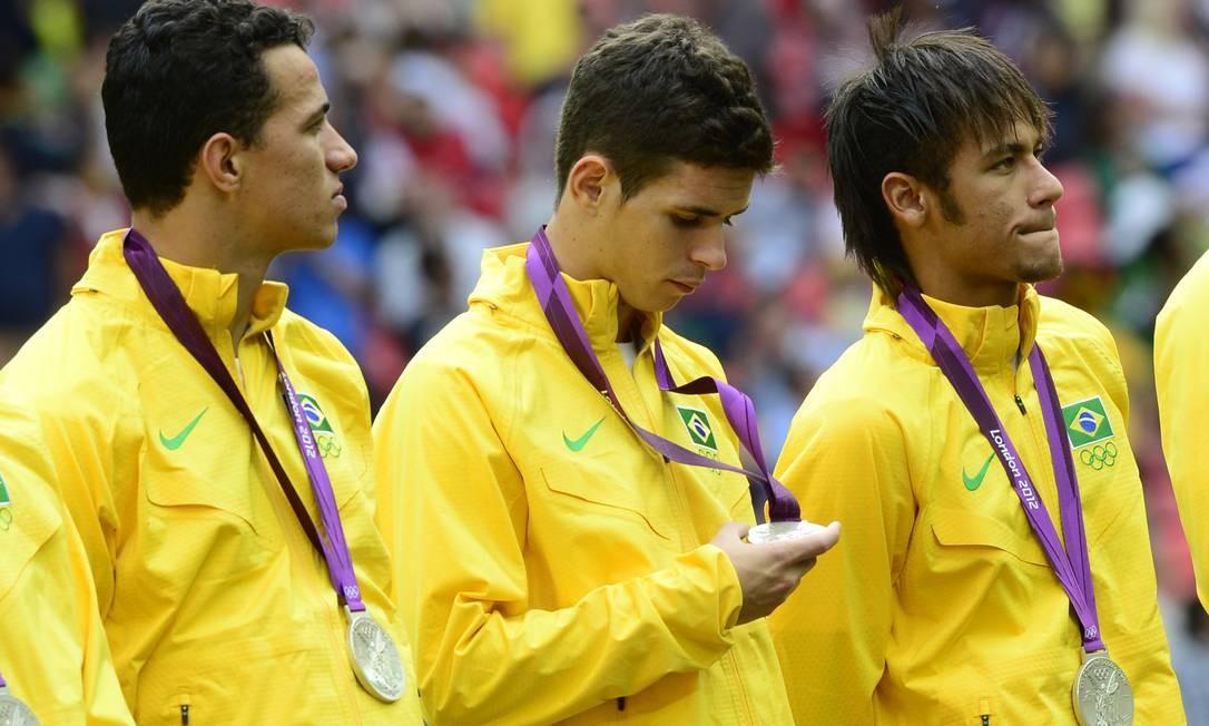 Ao lado de Fernando Damião e Neymar, o meia Oscar observa a medalha de prata no pódio Foto: DANIEL GARCIA / AFP