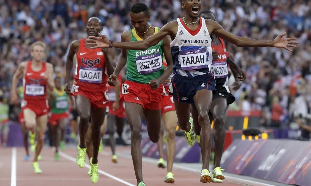 O britânico Mohamed Farah chega em primeiro na prova de 5.000 metros no Estádio Olímpico e comemora o ouro AP