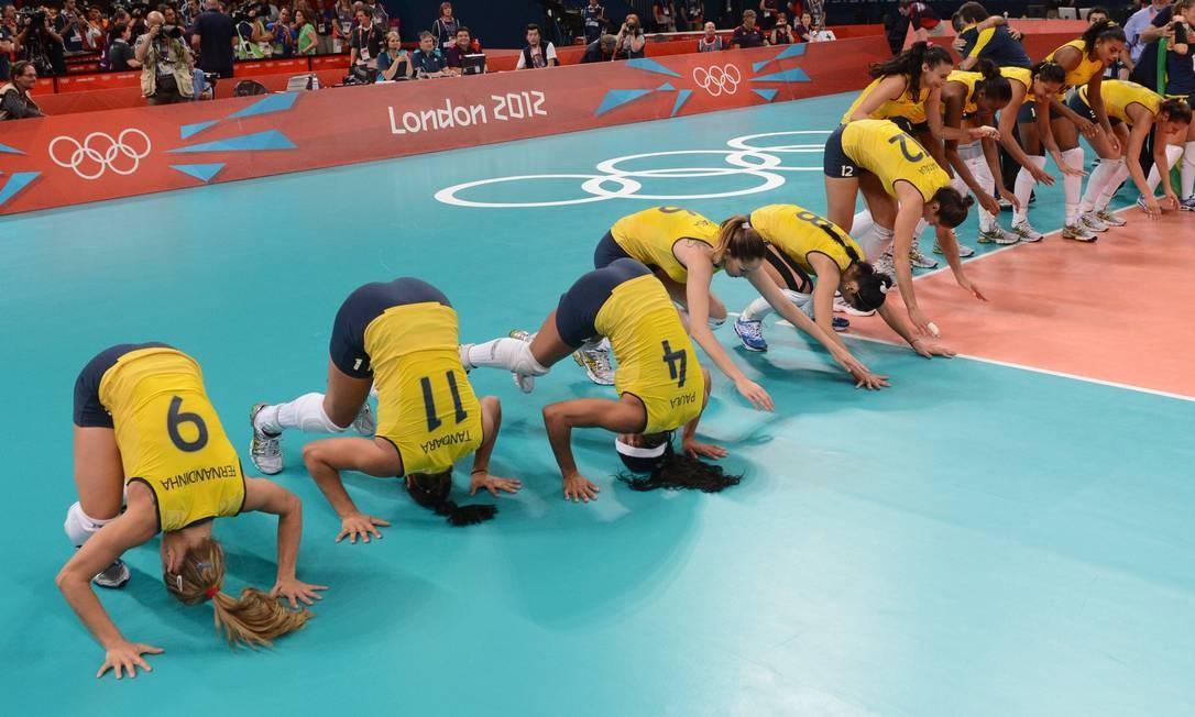 Meninas dão cambalhota coletiva para festejar na quadra a medalha de ouro no vôlei feminino Foto: AFP
