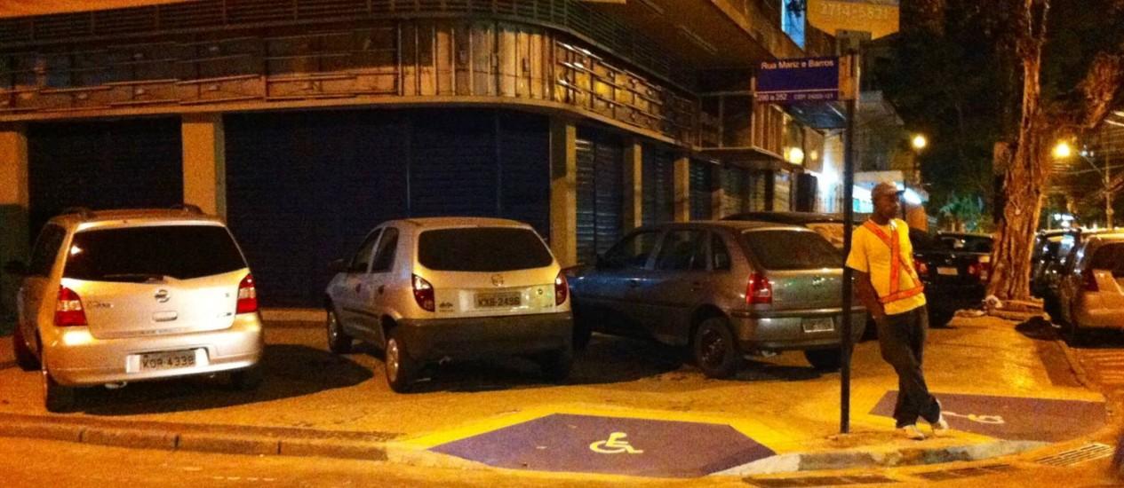 Encostado em placa, flanelinha toma conta de carros estacionados em cima do passeio Foto: Foto da leitora Cecilia Madeira / Eu-Repórter