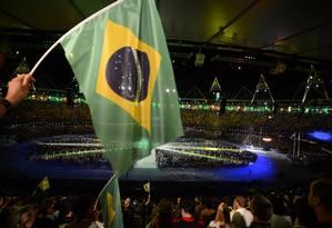 Um espectador balança a bandeira do Brasil na cerimônia de encerramento dos Jogos Olímpicos de Londres Foto: AFP PHOTO / JOHANNES EISELE