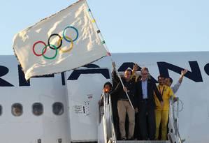 Eduardo Paes segura a bandeira olímpica durante a chegada do marco no Aeroporto Internacional Antônio Carlos Jobim Foto: Jorge William / Agência O Globo