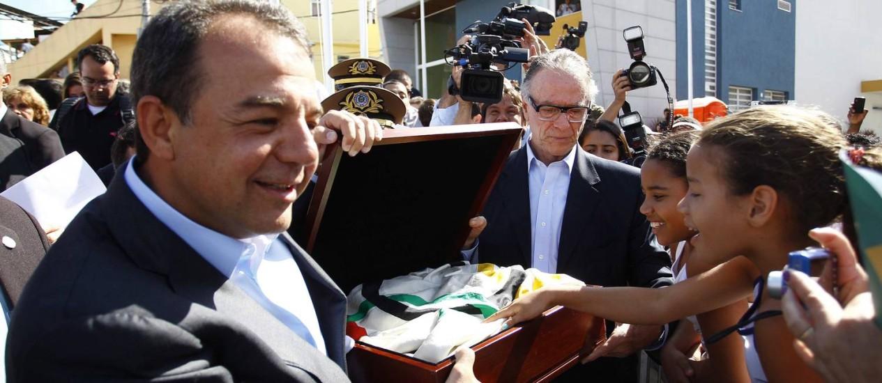 Governador Sérgio Cabral mostra a bandeira olímpica aos moradores do Complexo do Alemão Foto: Pablo Jacob / O Globo