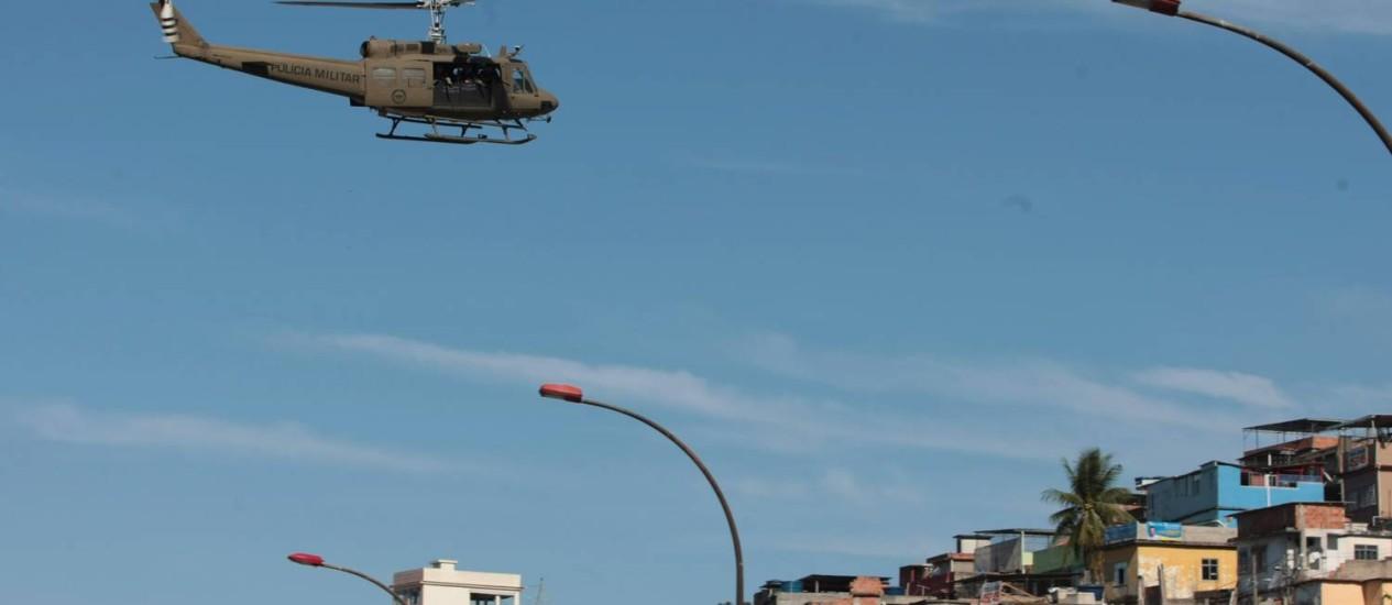 Helicóptero da Polícia Militar sobrevoa o Complexo da Maré Foto: Hudson Pontes / O Globo