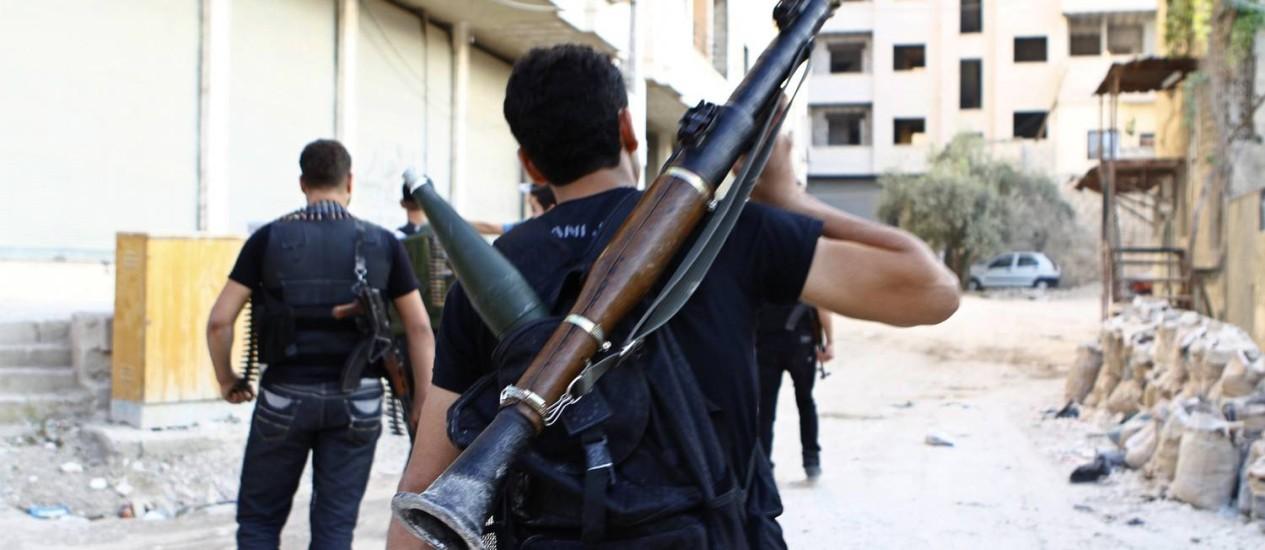 Um membro do Exército Livre da Síria caminha armado por uma rua de Damasco Foto: Reuters