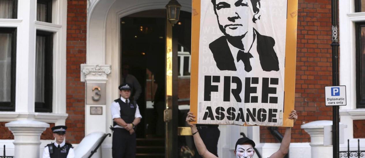 Um manifestante segura um cartaz em frente a embaixada do Equador em Londres, onde se encontra Julian Assange Foto: Neil Hall/Reuters