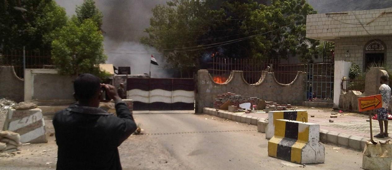 Um homem tira uma foto do local dos quartéis-generais do serviço de inteligência em Áden, onde um ataque deixou pelo menos 18 soldados mortos Foto: REUTERS