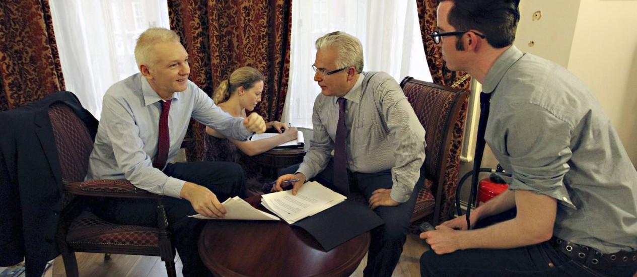 O fundador do site WikiLeaks, Julian Assange (à esquerda), com seu advogado Baltasar Garzón e duas outras pessoas não identificadas conversam dentro da embaixada do Equador em Londres, neste domingo Foto: AP