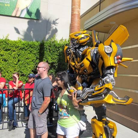 Turistas tiram fotos com o robô Bumblebee, na área dedicada aos Transformers na Universal Studios, em Los Angeles. Foto: Eduardo Maia / O Globo