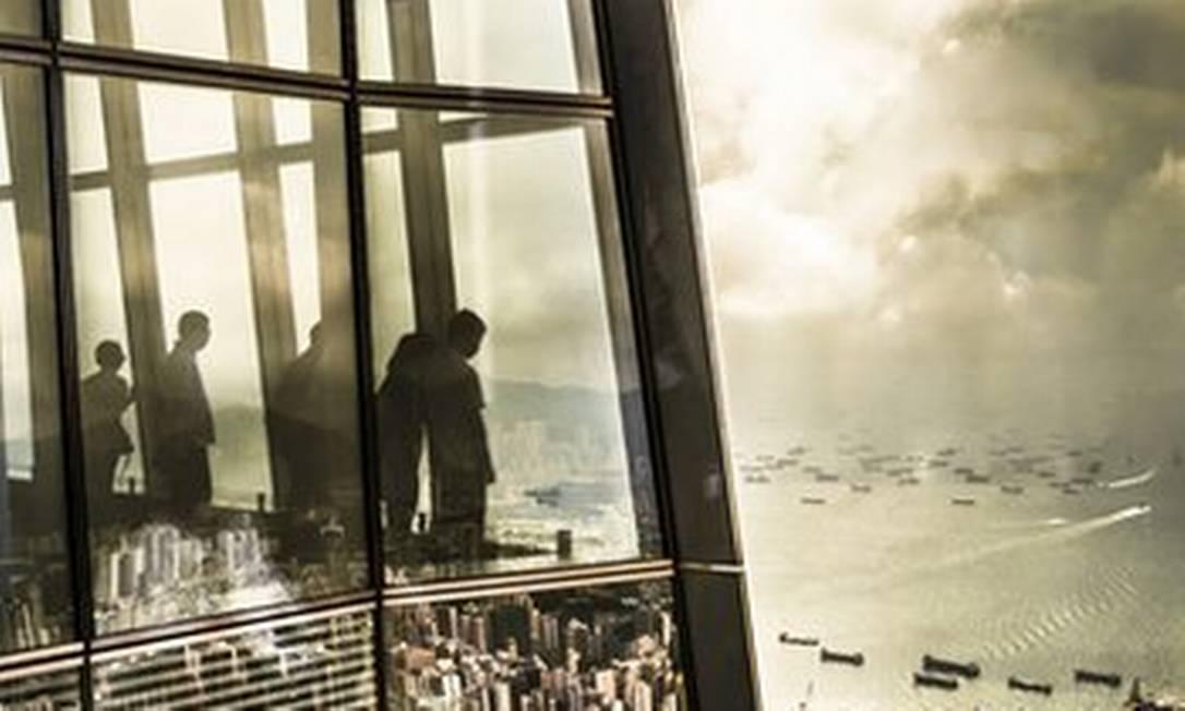 """""""A imagem mostra uma cena completa, dos reflexos de centenas de estruturas menores na cidade aos barcos na água e as pessoas dentro do prédio, assistindo ao mundo lá embaixo"""", diz o fotógrafo americano Tim Martin sobre seu trabalho, feito em Hong Kong Tim Martin"""