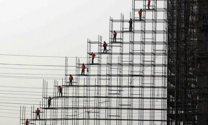 Nesta imagem de Kamal Krishore na Índia, trabalhadores formam uma fila nos andaimes para passar o material de construção uns para os outros Kamal Krishore