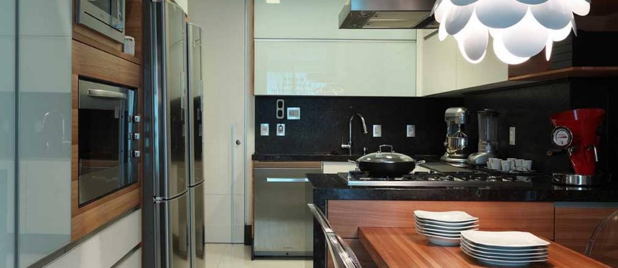 Na cozinha, a luminária moderna destaca o mobiliário de estilo mais clássico Foto: Divulgação
