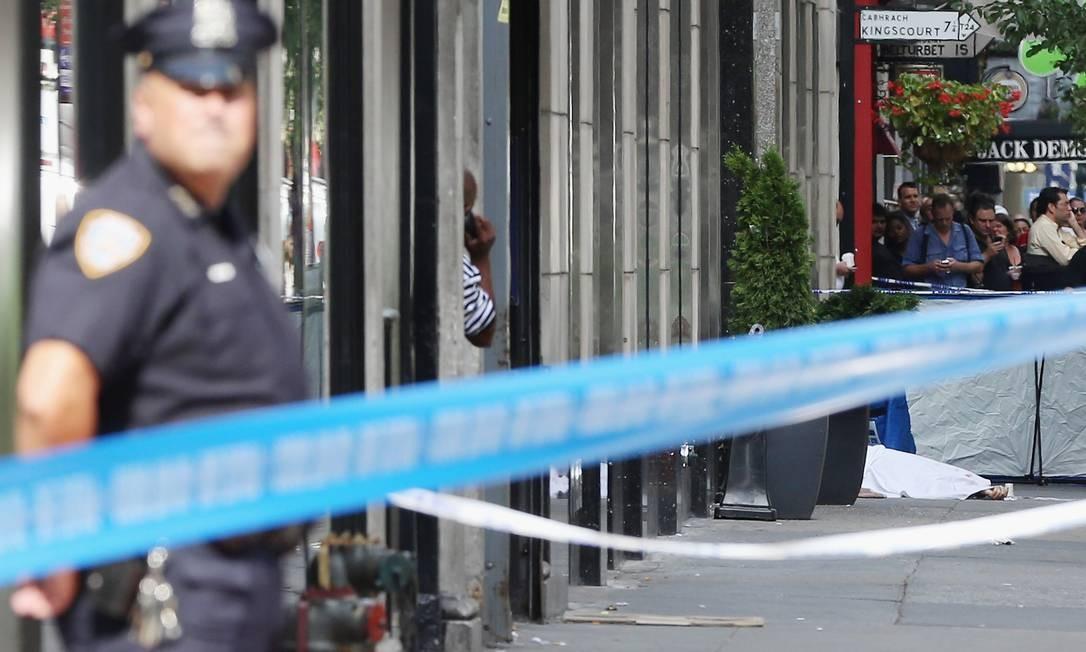 Policial isola uma área onde está o corpo de uma das vítimas do tiroteio Foto: Mario Tama/Getty Images/AFP