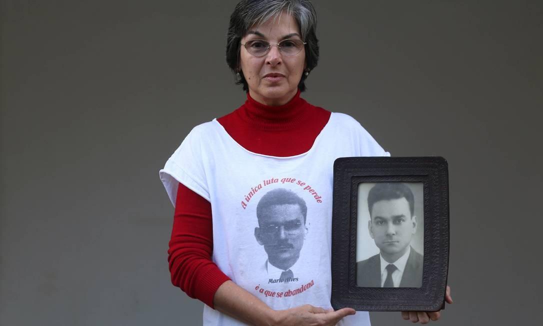 Lúcia Caldas Vieira segura um dos poucos retratos do pai que conseguiu guardar Foto: Agência O Globo / Camila Maia