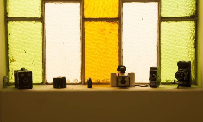 Num dos vitrais do sobrado, elas dispuseram sua coleção de máquinas fotográficas antigas Daniela Dacorso
