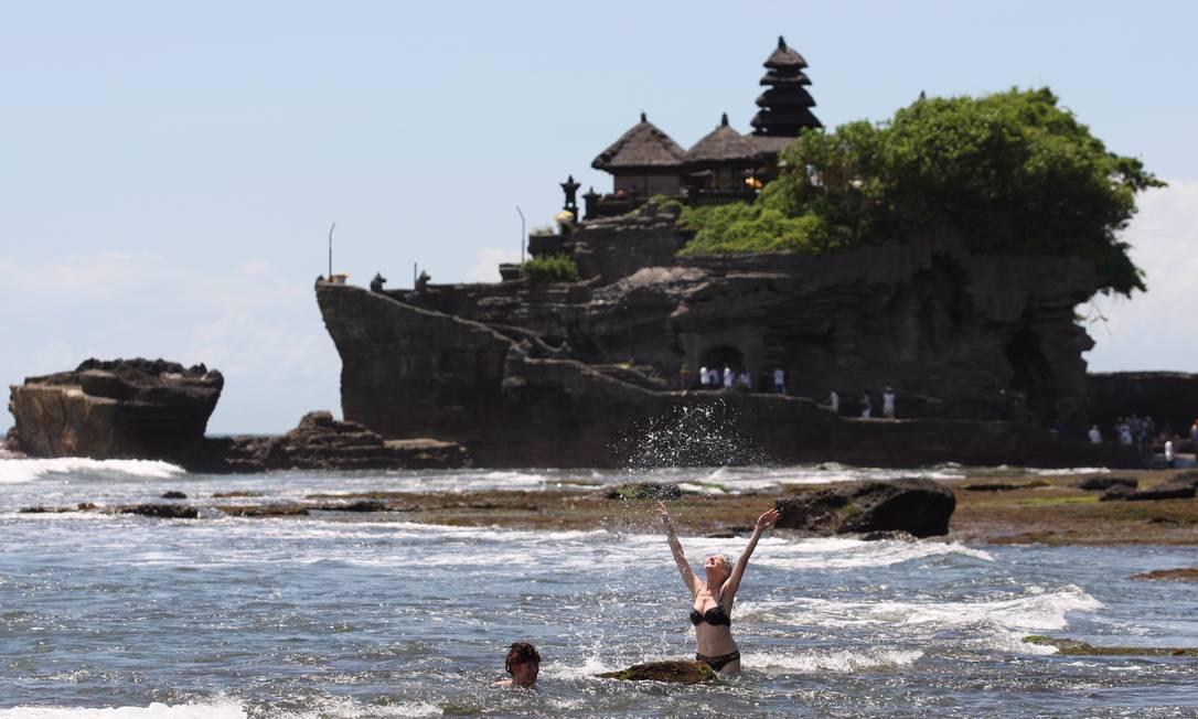 Banhistas na praia do templo de Oluwatu, em Bali, Indonésia. Foto: Marcelo Carnaval / O Globo
