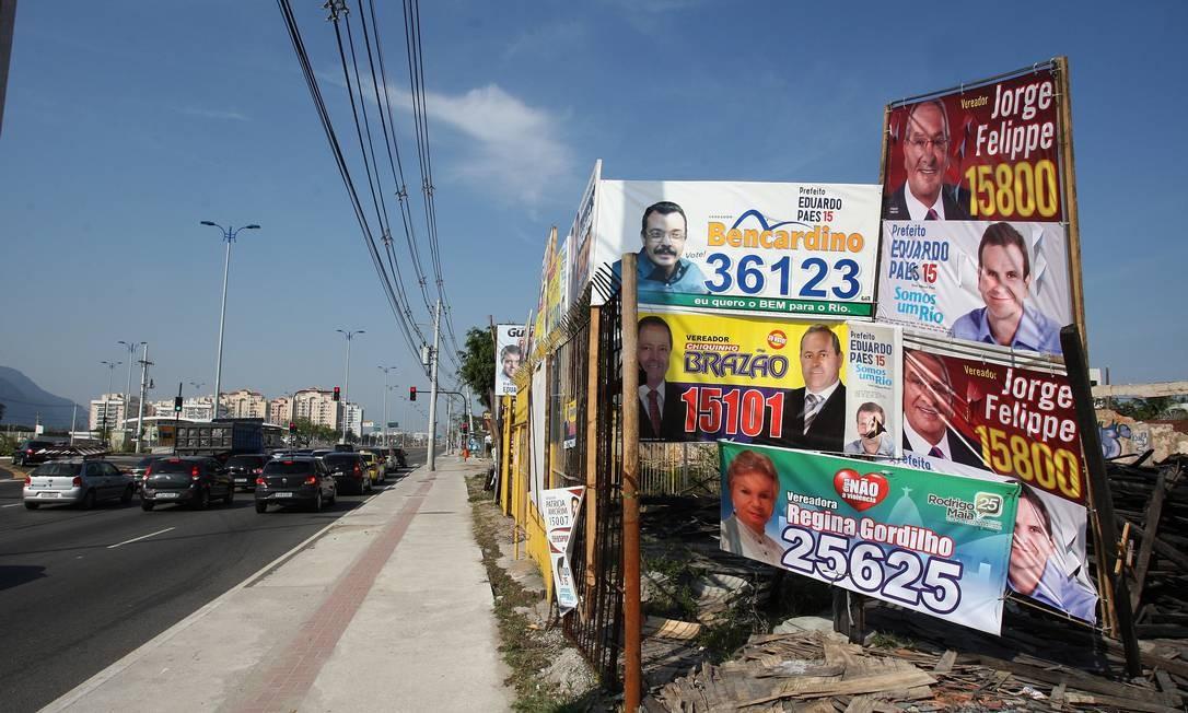 Poluição visual. Candidatos enchem de propaganda grade enferrujada de um terreno abandonado na Avenida das Américas Foto: Foto: Márcio Alves / O Globo