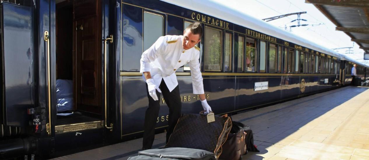 Luxo. Comissário de bordo arruma bagagem em frente ao Orient Express na estação de Bucareste, na Romênia Foto: RADU SIGHETI / REUTERS