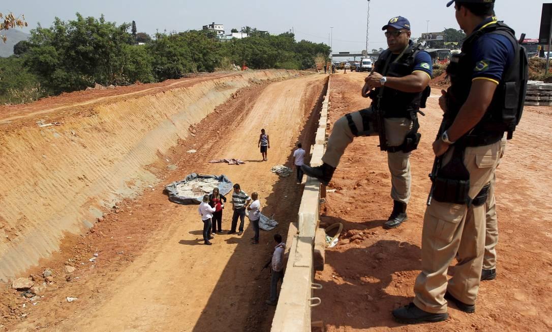 Policiais rodoviários federais observa o local onde os corpos foram encontrados Foto: Custódio Coimbra / O Globo