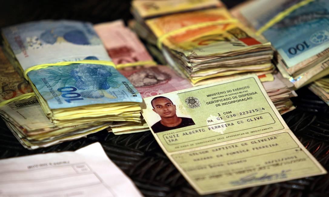 Documentos e dinheiro apreendidos com Luiz Alberto Ferreira de Oliveira, de 29 anos. Ele foi preso em casa, após uma informação ao disque-denúncia de que havia drogas e armas no local Gabriel de Paiva / O Globo