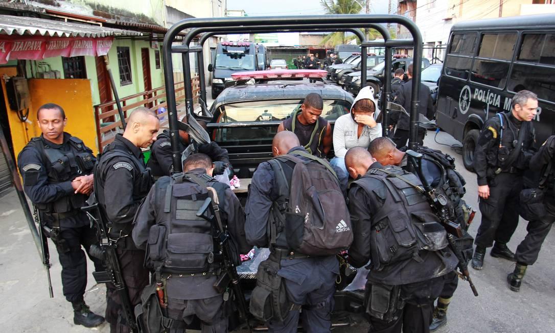 Policiais conferem o material apreendido com o casal Gabriel de Paiva / O Globo