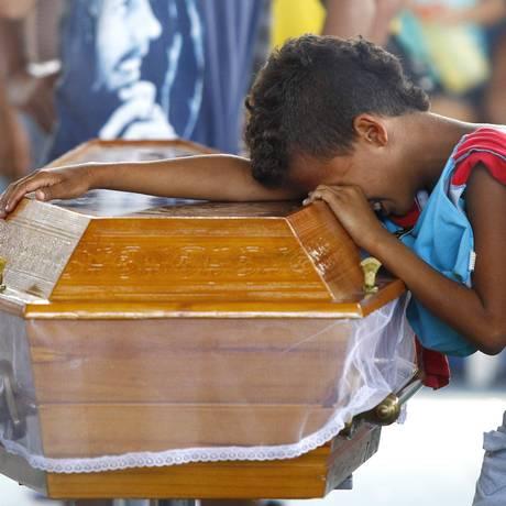 O menino Yago Teixeira, debruçado sobre o caixão de Patrick Machado, chora a morte do amigo durante o velório em Nilópolis, na terça-feira Foto: Pablo Jacob / O Globo
