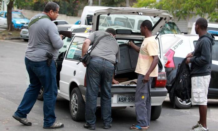 Policiais revistam veículo no interior da favela Gabriel de Paiva / O Globo