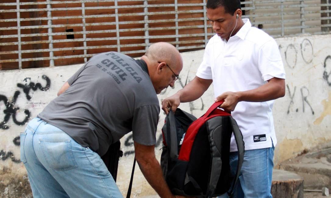 Morador tem a mochila revistada Foto: Gabriel de Paiva / O Globo
