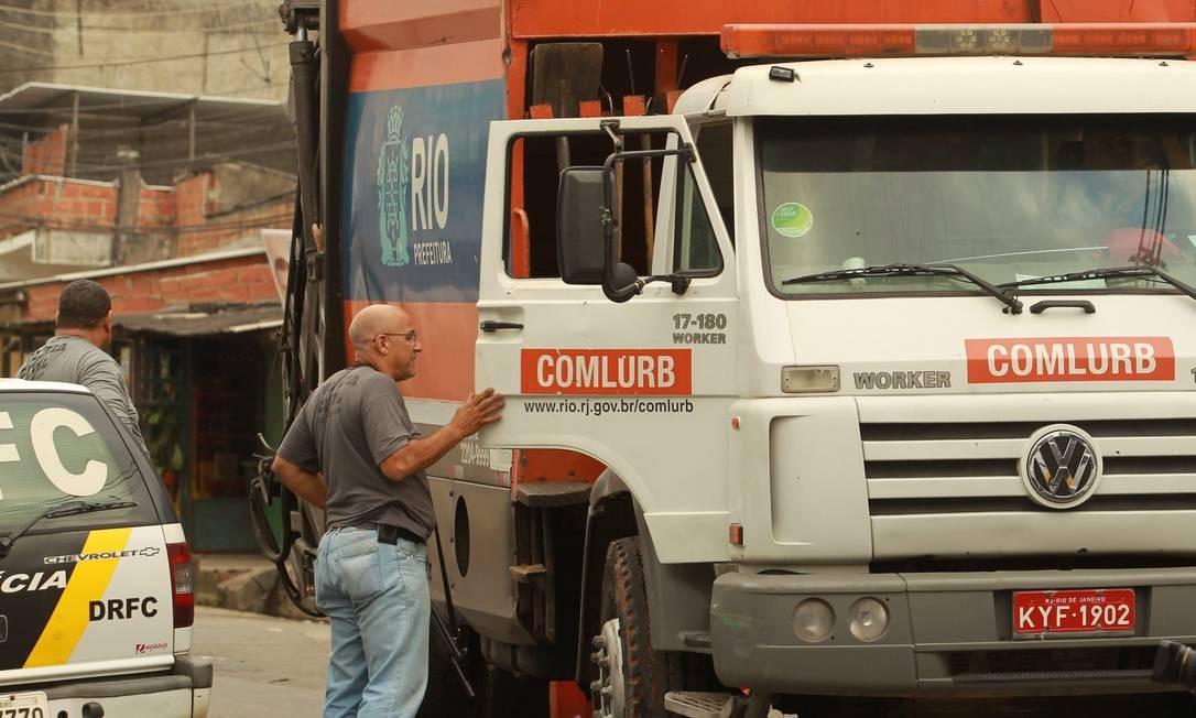 Agente da Polícia Civil revista caminhão da Comlurb Foto: Gabriel de Paiva / O Globo
