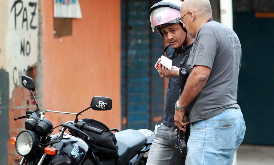 Motociclista apresenta documentos ao policial civil Foto: Gabriel de Paiva / O Globo