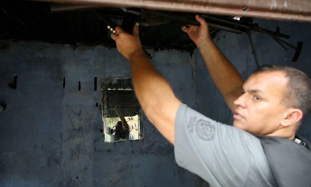 Policial encontra metralhadora .30 no interior da comunidade Foto: Pablo Jacob / O Globo