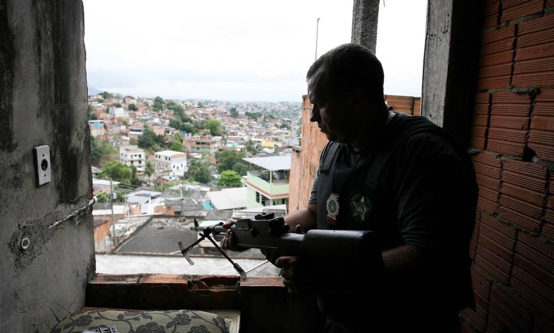 Policial observa a favela de uma das casas no alto da comunidade Foto: Pablo Jacob / O Globo