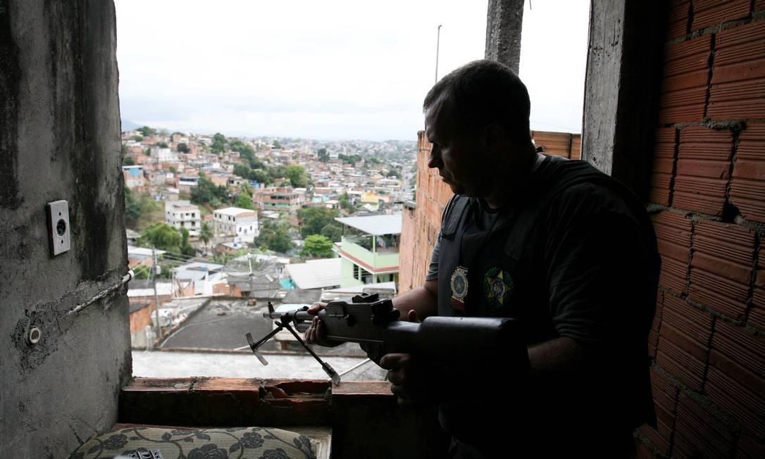 Policial observa a favela de uma das casas no alto da comunidade Pablo Jacob / O Globo