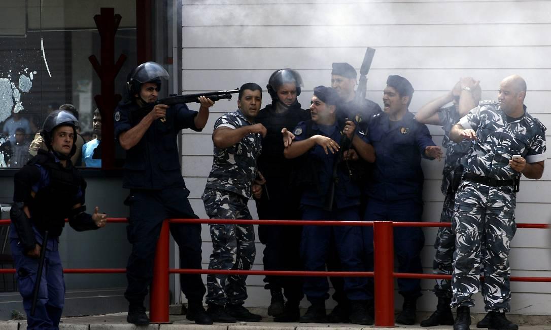 A polícia foi chamada para tentar controlar a situação, mas os manifestantes acabaram colocando fogo no local STR / AFP