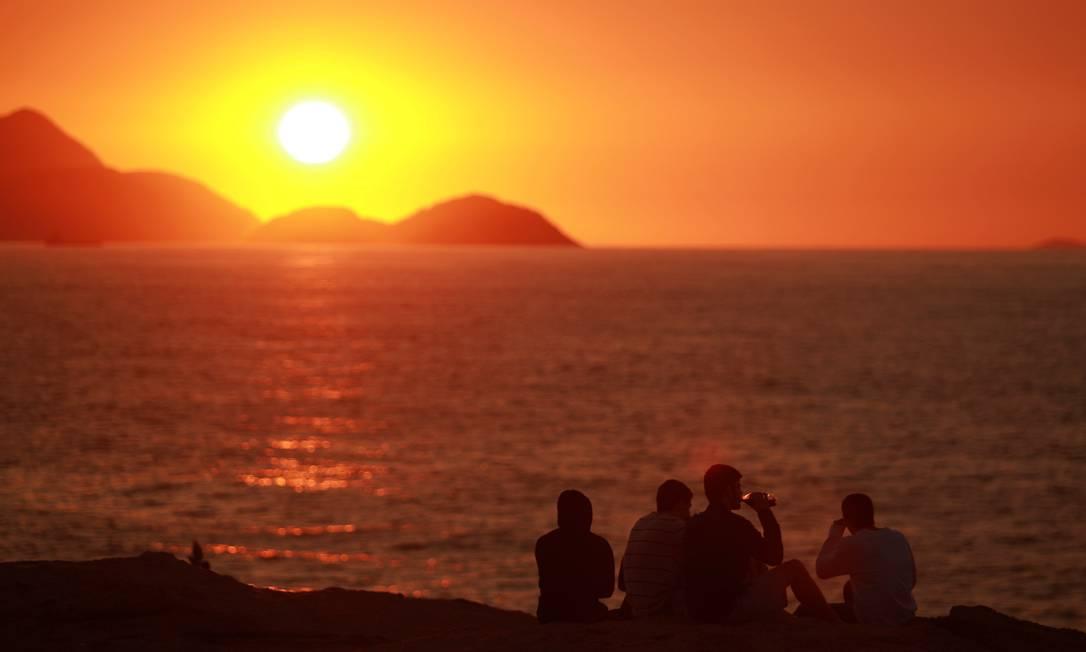 Jovens observam o nascer do sol na Praia do Arpoador, na manhã deste sábado Gabriel de Paiva / O Globo
