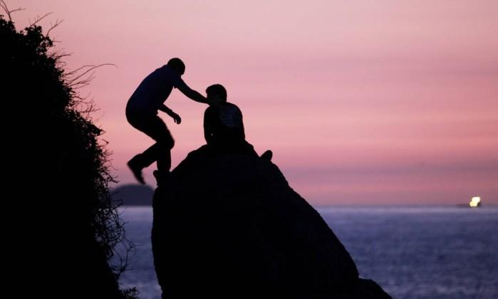Jovens guardam lugar numa pedra para assistir ao belo nascer do sol na Praia do Arpoador Gabriel de Paiva / O Globo