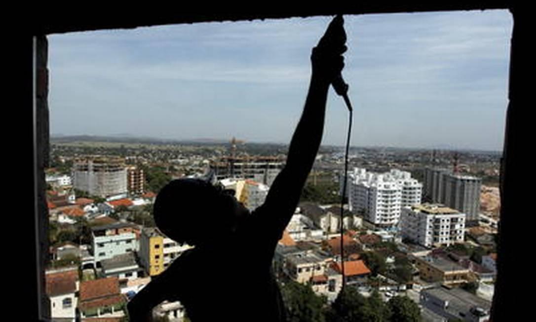 Obras em série. Operário trabalha num dos 30 empreendimentos em construção em Itaboraí por causa do Comperj Foto: Custódio Coimbra / O Globo