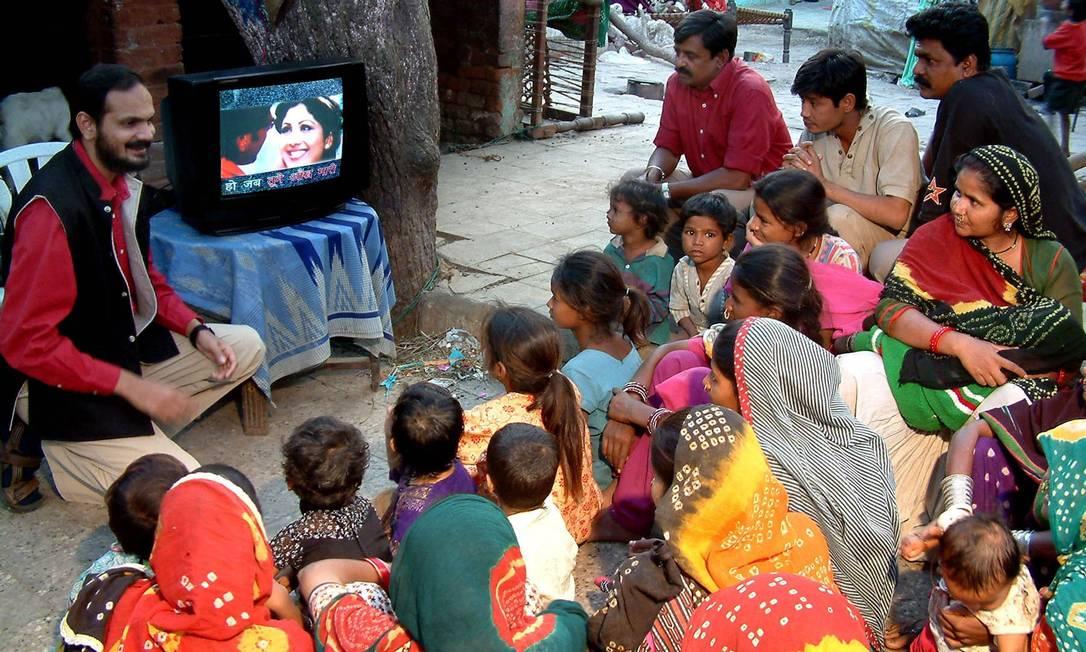"""Na telinha. Brij Kothari, fundador da PlanetRead, exibe o programa que criou inserindo legendas em hindi na programação de TV: fonética e grafia levam a um """"aprendizado automático"""" Foto: Divulgação/PlanetRead"""