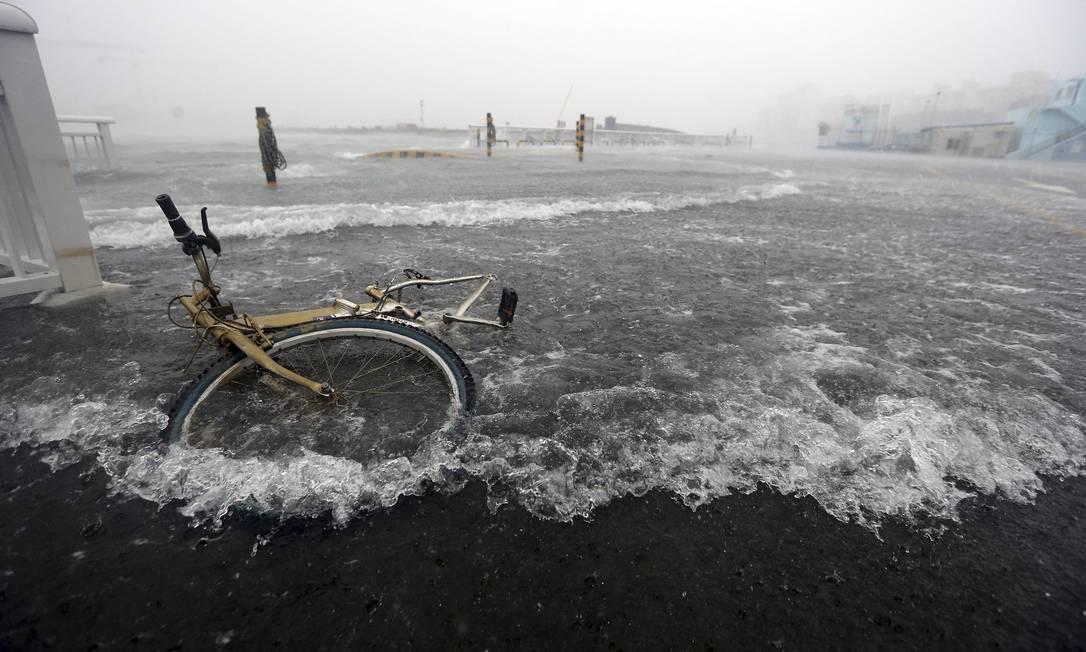 No porto de Tongyeong, uma bicicleta é arrastada pelas águas YONHAP / REUTERS