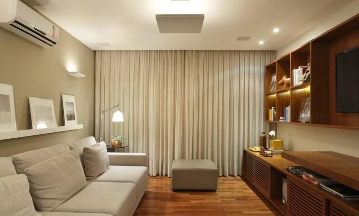 O sofá, em tecido de tom neutro, e os quadros apoiados na prateleira, dão charme ao cantinho de lazer do apartamento de 200 metros quadrados Denílson Machado/MCA Estúdio