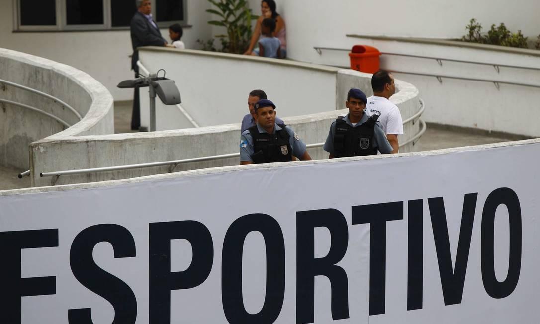 Policiais montam guarda na entrada do centro esportivo da comunidade Foto: Pablo Jacob / O Globo