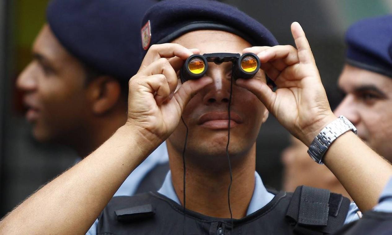 Com binóculos, policial olha para as casas da comunidade Foto: O Globo