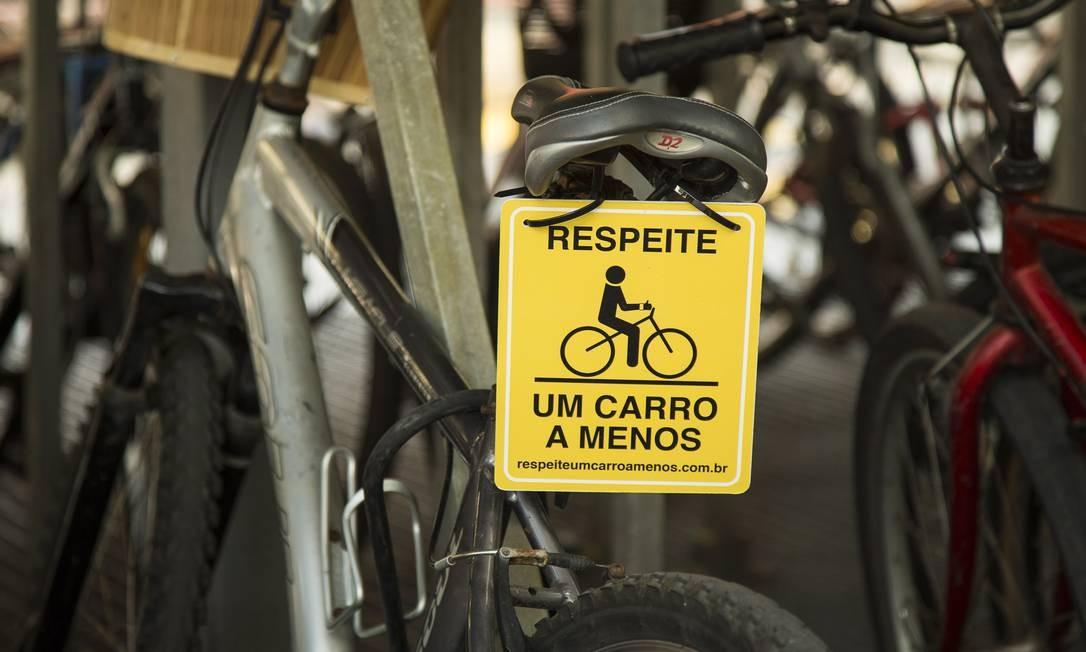 Placa de campanha pede respeito ao ciclista no trânsito numa bicicleta estacionada na PUC Foto: Leo Martins / O Globo