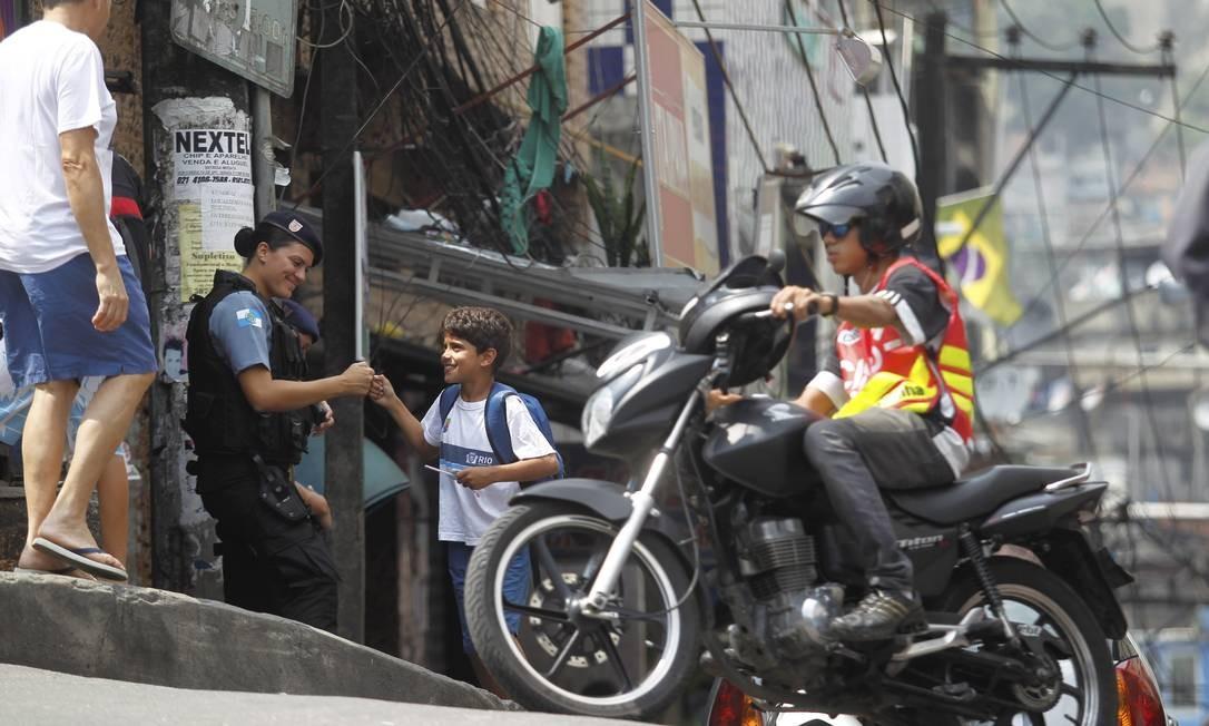 Relação amigável. PM cumprimenta um menino a Rocinha, um dia após a inauguração da UPP Foto: Custódio Coimbra / O Globo