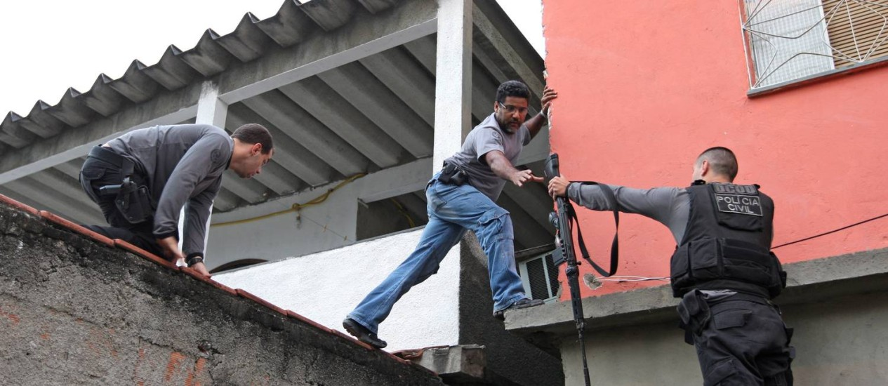Policiais pulam o muro de uma casa durante operação Foto: Urbano Erbiste / Extra / Agência O Globo