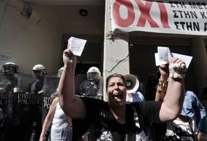 Uma enfermeira que não recebe salário há cinco meses de uma clínica privada mostra fatura de eletricidade que deixou de pagar durante manifestação contra o governo em Atenas Foto: LOUISA GOULIAMAKI / AFP