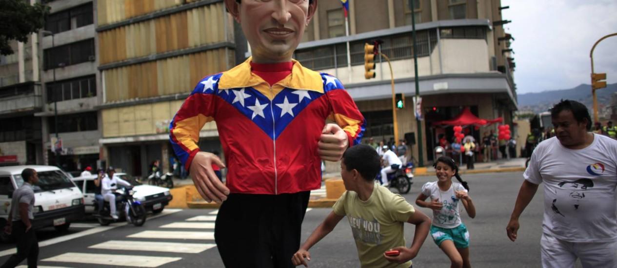 Boneco do presidente Hugo Chávez atravessa a rua em Caracas: em ano eleitoral, aumento de gastos públicos e de importações afetam a economia venezuelana Foto: AP/27-9-2012