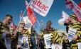 Manifestantes vestidos com trajes de prisioneiros e cartazes com a foto do presidente da França, François Hollande, protestam em Paris