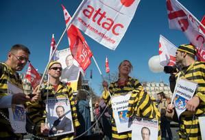 Manifestantes vestidos com trajes de prisioneiros e cartazes com a foto do presidente da França, François Hollande, protestam em Paris Foto: AFP